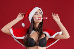 Sexy woman in the clothes of Santa Claus with Christmas candy Stock Image