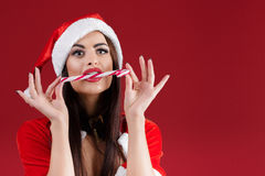 Sexy woman in the clothes of Santa Claus with Christmas candy Royalty Free Stock Photo