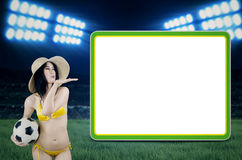 Sexy woman with copyspace at stadion. Sexy woman wearing bikini posing with a soccer ball next to copyspace at a soccer stadion Stock Image