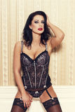 Sexy woman in corset posing at wall Stock Images