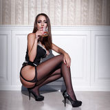 Sexy woman in corset and stockings squat with whiskey Royalty Free Stock Photos