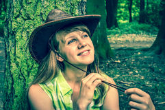 Woman with cowboy hat in park - retro style. Woman with leather cowboy hat in park - retro style Stock Images