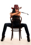 Woman in cowboy hat sits on chair. Isolated on white Stock Photo