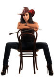 Sexy woman in cowboy hat sits on chair Stock Images