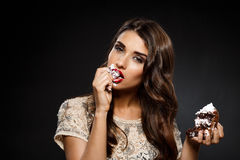 Sexy woman in creamy dress holding piece of cake Stock Photography