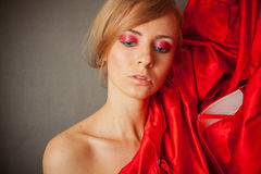 Sexy woman with curly hair and red sillk drapery close to her fa. Young caucasian model under 30 with red smoky eyes makeup Royalty Free Stock Photography