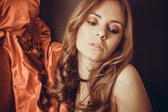 Sexy woman with curly hair and red sillk drapery close to her fa. Young caucasian model under 30 with red smoky eyes makeup Stock Image