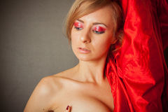 Sexy woman with curly hair and red sillk drapery close to her fa. Young caucasian model under 30 with red smoky eyes makeup Stock Photos
