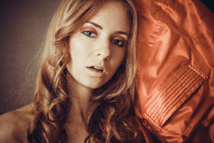 Sexy woman with curly hair and red sillk drapery close to her fa. Young caucasian model under 30 with red smoky eyes makeup Stock Photography