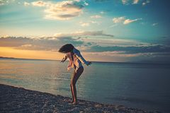 Woman dance on Caribbean sea in Bahamas at sunset. Girl relax on pebble beach fashion swimsuit. Summer vacation and. Travel to ocean. Fashion and beauty look royalty free stock image
