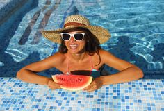 Sexy woman with dark hair eating watermelon. In the pool Stock Images