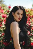 woman with dark hair in elegant black dress posing in bloss stock photography