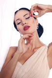Sexy woman with dark hair with evening makeup and bijou. Fashion interior photo of beautiful sexy woman with dark hair with evening makeup and bijou Stock Image