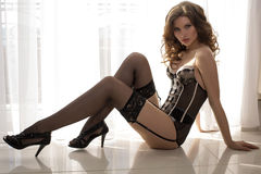 Sexy woman with dark hair in lingerie posing at bedroom Stock Images