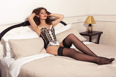 Sexy woman with dark hair in lingerie posing at bedroom Royalty Free Stock Images