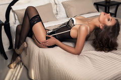 Sexy woman with dark hair in lingerie posing at bedroom Stock Photo