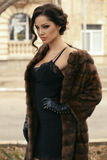 Woman with dark hair in luxurious fur coat and gloves. Fashion outdoor photo of beautiful sensual woman with dark hair wearing luxurious fur coat and leather royalty free stock images