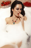 Sexy woman with dark hair posing in bath with foam. Fashion interior photo of sexy woman with dark hair posing in bath with foam,eating strawberry Stock Photo