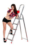 Sexy woman decorator. Leaning against a ladder Stock Photo