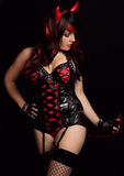 Sexy Woman in Devil Costume. An image of an attractive woman in a black and red latex devil costume with horns and tail Stock Photography