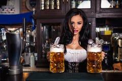 woman in dirndl dress holding Oktoberfest beer stein. Stock Image