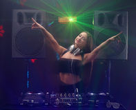 Sexy woman dj playing music on mixer and dancing with light beam. Young sexy woman dj in headphones playing music on mixer on table Royalty Free Stock Image