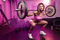 Sexy woman doing squat workout in gym. Beautiful sporty sexy woman doing squat workout in gym Royalty Free Stock Photos