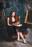 Sexy woman in dress sitting in armchair with a barbecue Royalty Free Stock Image