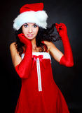 Woman dressed as Santa. Studio portrait of a young brunette woman dressed as Santa against dark background royalty free stock images