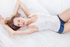 Sexy woman dressed in denim shorts and white lying on a bed. Sexy blond woman dressed in denim shorts and white lying on a bed Stock Photos