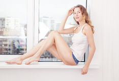 woman dressed in denim shorts and white lying near window royalty free stock photo