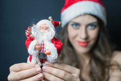 Sexy woman dressed in Santa Claus clothes gives you toy Stock Photo
