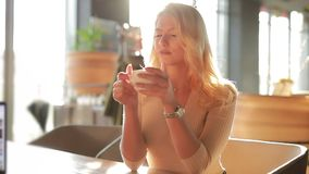 Sexy woman drinking coffee. Or latte sitting and relaxing in cafe at the morning, bright sunlight indoor, slow motion stock video footage