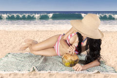 Sexy woman drinks a coconut water on beach Stock Image