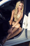 Sexy woman driver with blond hair posing in luxury auto Royalty Free Stock Photography