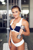 Sexy woman with dumbbell workout in gym Stock Image