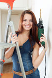 Sexy woman in dungarees with drill Royalty Free Stock Images
