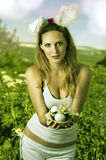 Sexy woman easter bunny. On spring meadow with flowers Stock Photos