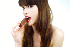 Sexy woman eating a bar of chocolate - studio shot Stock Photos
