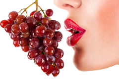 Sexy woman eating red grapes, sensual red lips Royalty Free Stock Photos