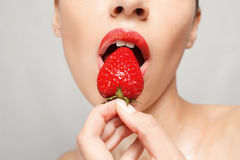 Sexy Woman Eating Strawberry. People, emotions, natural, food, beauty and lifestyle concept - Sexy Woman Eating Strawberry. Sensual Lips. Manicure and Lipstick Stock Images