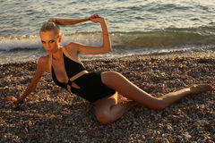 Sexy woman in elegant swimsuit, relaxing on sunset beach Royalty Free Stock Photos