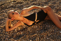 Sexy woman in elegant swimsuit, relaxing on sunset beach Royalty Free Stock Image