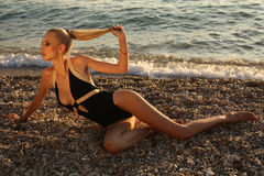 woman in elegant swimsuit, relaxing on sunset beach Stock Images