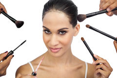 Sexy woman encircled by make up brushes. On white background Stock Photos