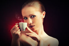 Sexy woman enjoying a hot cup of coffee on a dark background Stock Image