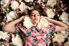 Woman with eyes closed lying down on flowers. In studio photo. Beauty concept. Floral decoration stock image