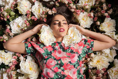 Woman with eyes closed lying down on flowers. In studio photo. Beauty concept. Floral decoration stock images