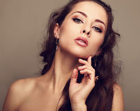 Sexy woman in fashion earrings touching clean face Royalty Free Stock Image