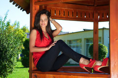 Sexy woman in fashionable outfit sitting on outdoor wooden gazeb Stock Photo